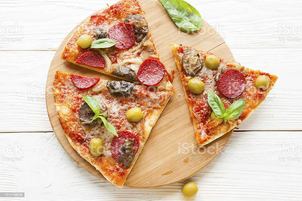 cut in pizza with cheese, mushrooms and salami on board royalty-free stock photo