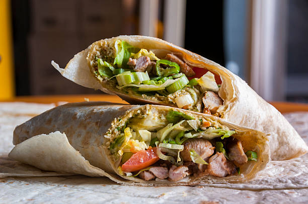 cut indian wrap with chicken meat and garam masala - mahroch stock pictures, royalty-free photos & images