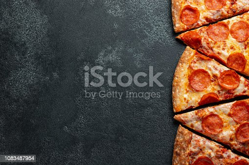 istock Cut into slices delicious fresh pizza with sausage pepperoni and cheese on a dark background. Top view with copy space for text. Pizza on the black concrete table. flat lay 1083487954