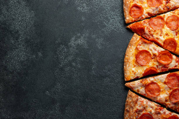 Cut into slices delicious fresh pizza with sausage pepperoni and cheese on a dark background. Top view with copy space for text. Pizza on the black concrete table. flat lay Cut into slices delicious fresh pizza with sausage pepperoni and cheese on a dark background. Top view with copy space for text. Pizza on the black concrete table. flat lay. pizza stock pictures, royalty-free photos & images