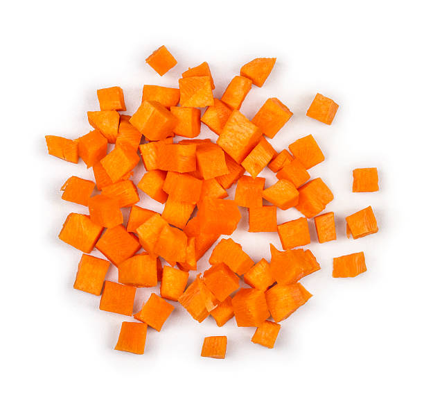 cut into squares pieces of carrot on a white background cut into squares pieces of carrot on a white background chopped food stock pictures, royalty-free photos & images