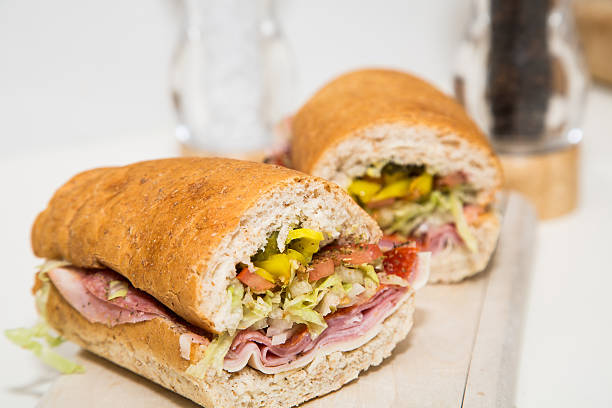 Cut Italian Sub on Wood Cutting Board A fresh italian sub sandwich with sliced meat, vegetables on baked bread submarine sandwich stock pictures, royalty-free photos & images