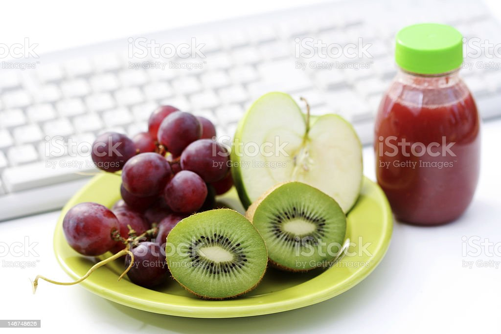 Cut kiwi, grapes, and an apple to snack on while working royalty-free stock photo