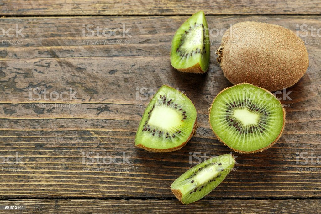 cut kiwi on a wooden background, the texture of the fruit is clearly visible. royalty-free stock photo