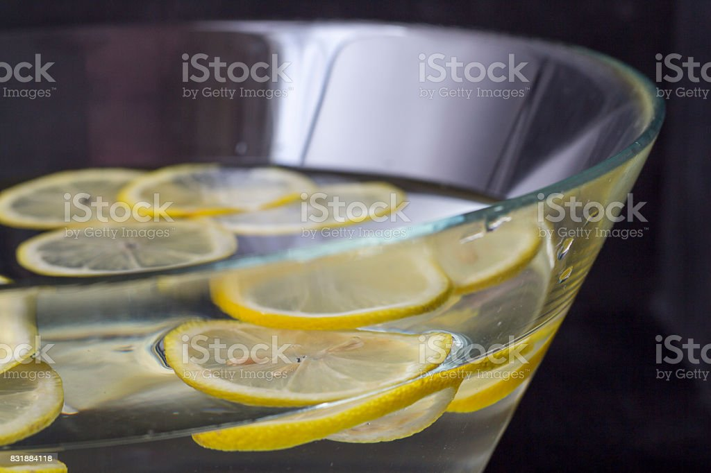 Cut Lemon slices in bowl of water for hand washing stock photo