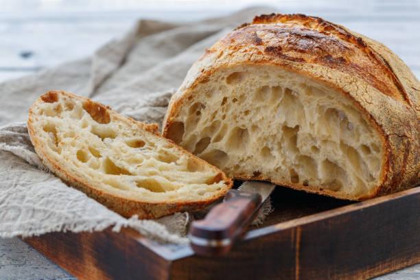 Cut loaf of artisanal wheat bread on sourdough. stock photo