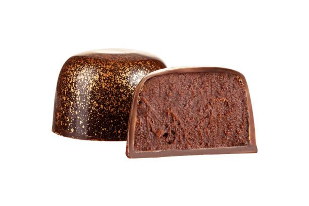 Cut luxury handmade bonbon with chocolate ganache filling isolated on white background