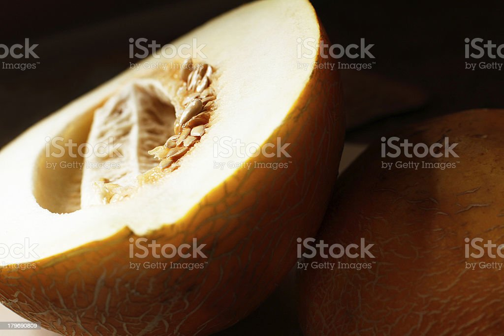 Cut melon with seeds on dark background royalty-free stock photo