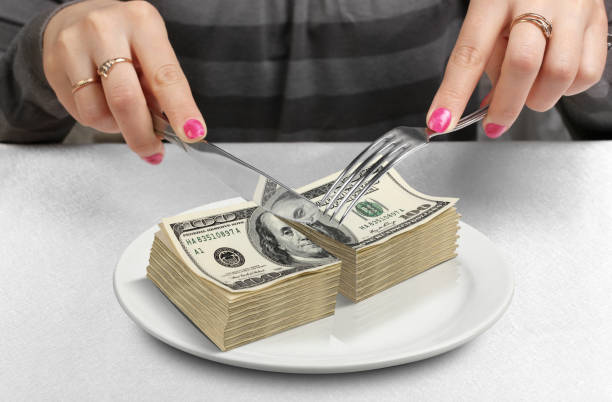 Cut money on plate, cut budget concept stock photo