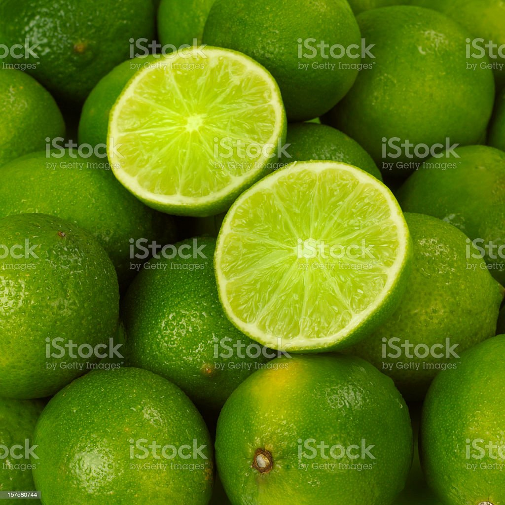 A cut open lime atop a pile of fresh limes stock photo