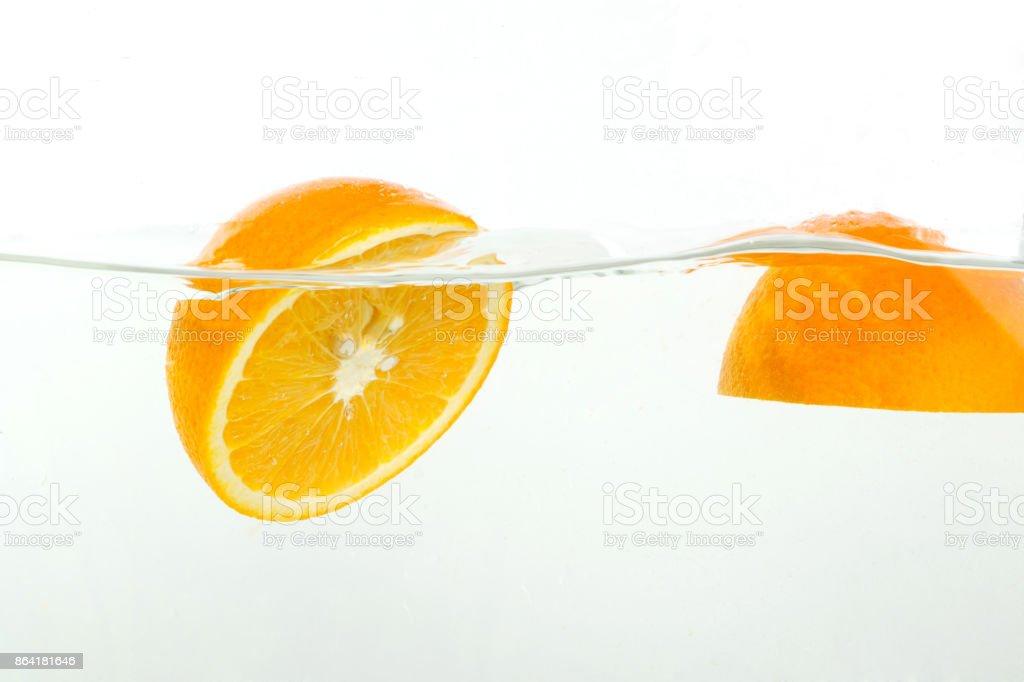 cut orange falls into water, splashes on white background, close-up royalty-free stock photo