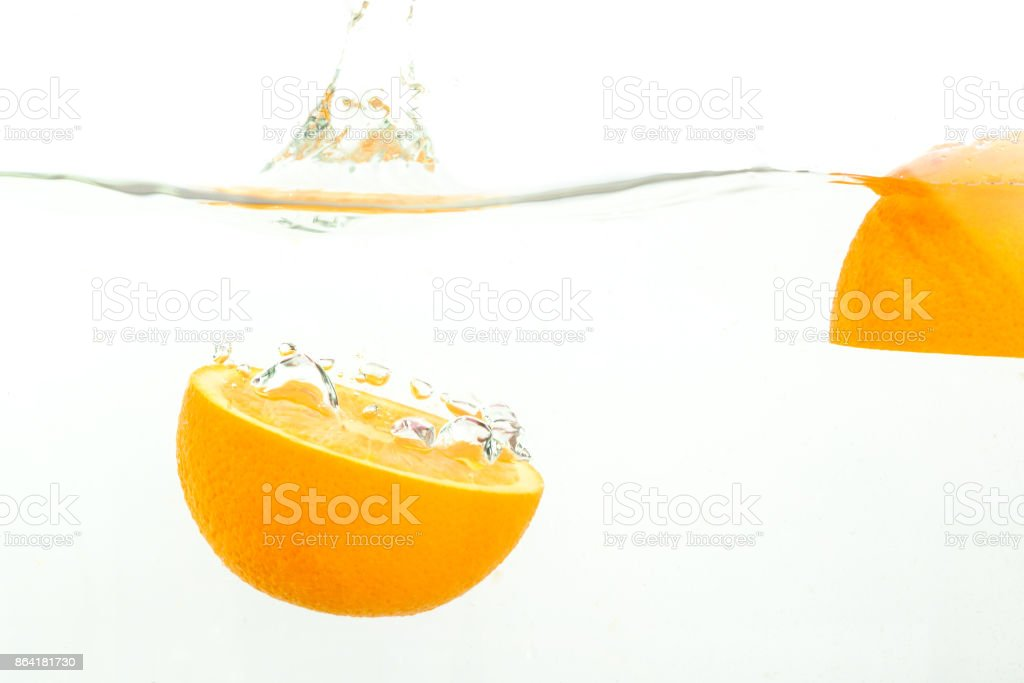 cut orange falls into water, splashes on white background, close-up royalty-free stock photo