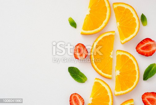 istock cut orange, strawberry and mint leaves on white background 11 1006041990
