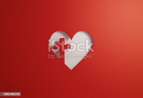 Cut out heart shape with a cross on red background. Great use for Good Friday and faith concepts. Horizontal composition with copy space.