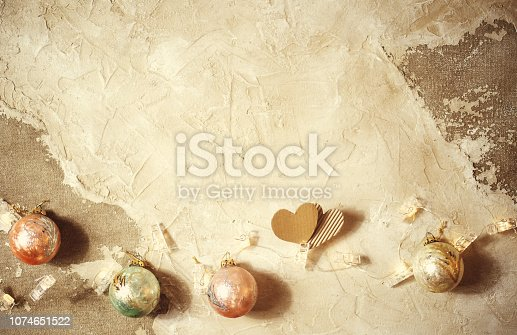 istock Cut out hearts on grunge texture table with christmas balls 1074651522