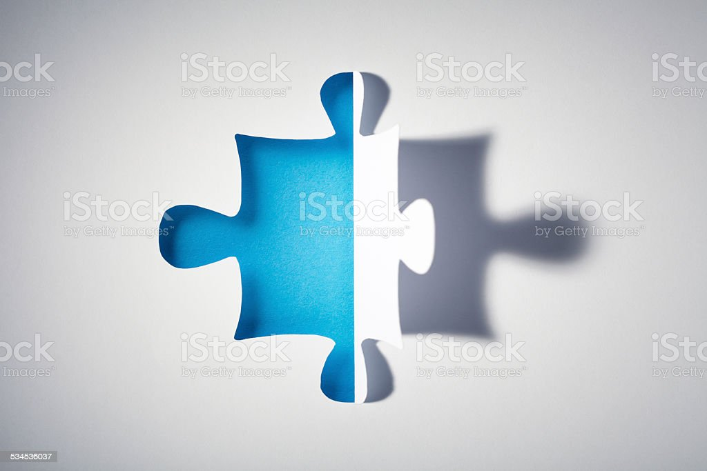 Macro photography of a puzzle piece cutted into a white sheet of...