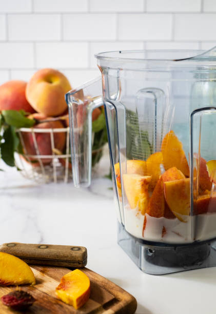Cut Peaches and Plant-Based Milk in a Blender stock photo
