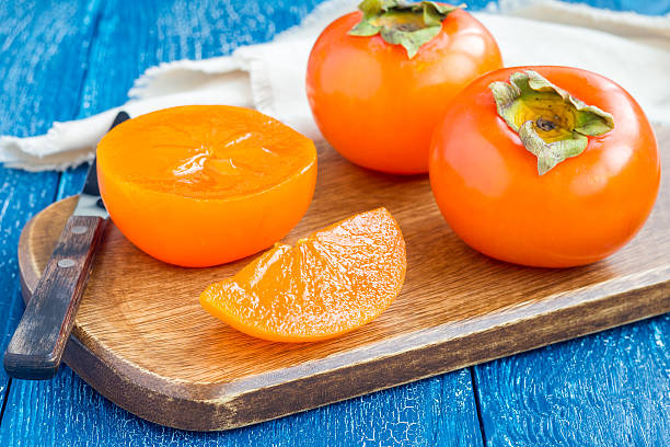 cut persimmon fruits on wooden board and table, horizontal - 柿 ストックフォトと画像