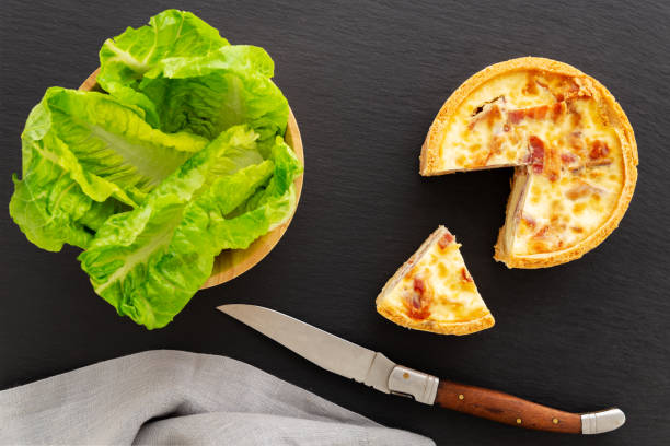 Cut quiche Lorraine, tart, flat lay, with salad and knife on a slate. stock photo