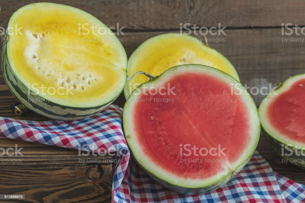 Cut red and yellow watermelons on a wooden box in a vintage wooden background in rustic style, selective focus, toned photo. royalty-free stock photo