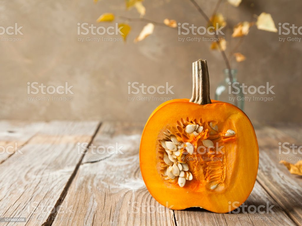 Cut ripe orange pumpkin with seeds and fallen leaves on pastel brown background. - Foto stock royalty-free di Alimentazione sana