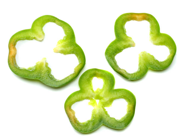 cut slices of green sweet bell pepper isolated on white background stock photo