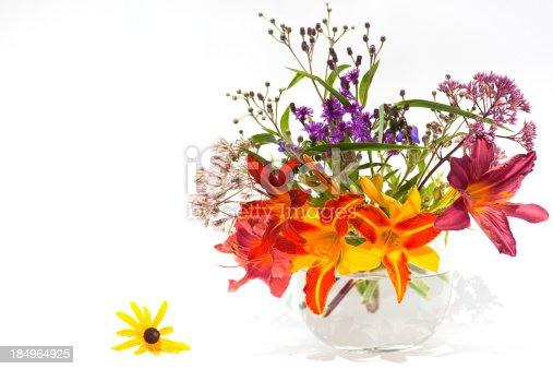 A glass vase of cut vibrant summer flower and lilies against a white background.