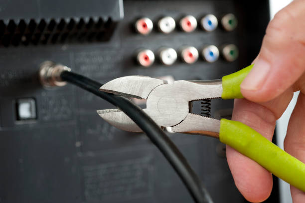 Cut the cable TV cord with hand and wire cutters stock photo