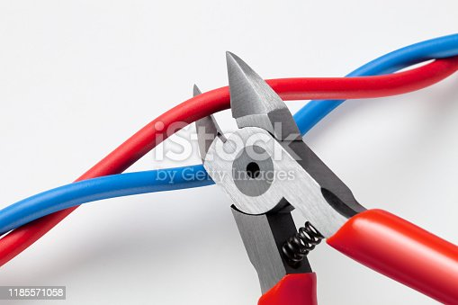 Metal nippers is cutting red wire and leaving blue on white background.