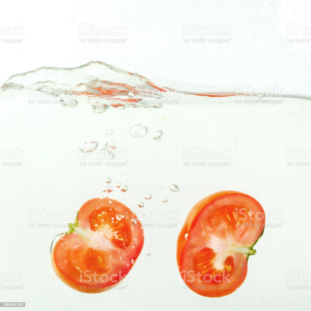 cut tomato falls into the water, splashes on white background, close-up royalty-free stock photo