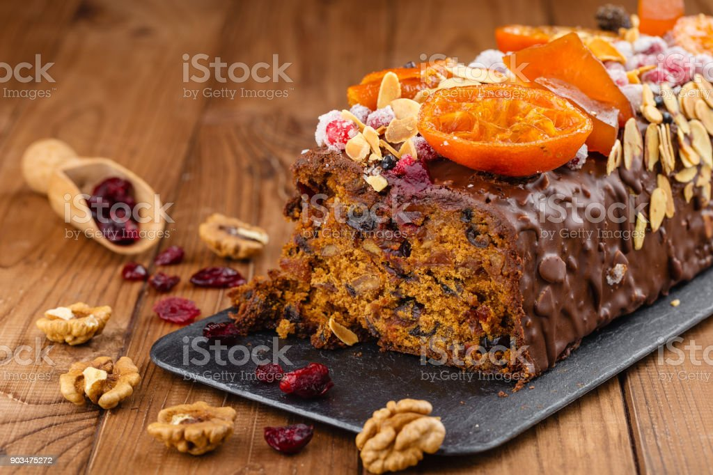 Cut traditional christmas fruit cake pudding in chocolate glaze stock photo