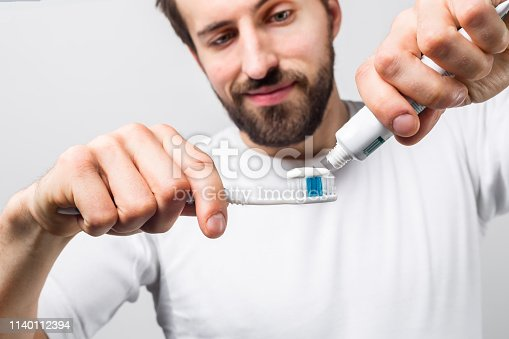 Cut view of a man putting some tooth paste on a tooth brush. He wants to clean his teeth. Guy looks happy and satisfied. Close up. Isolated on white background