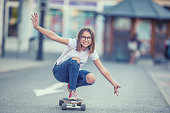 Cut young skater girl riding on her longboard in the city.