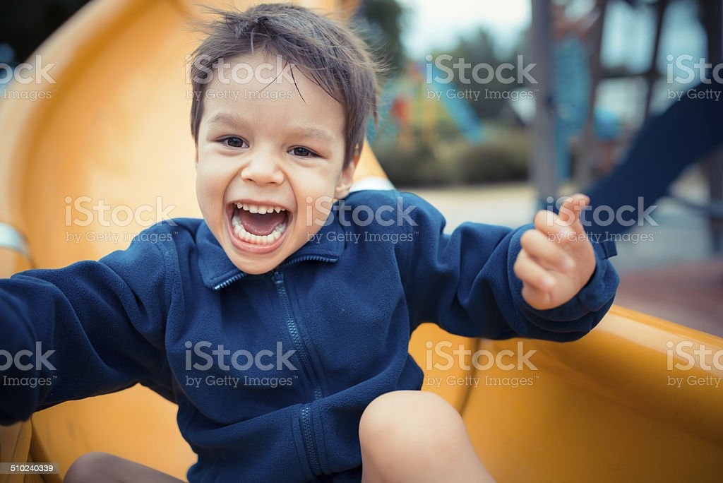 A young 3 year old Asian Caucasian boy plays on a yellow slide in a...