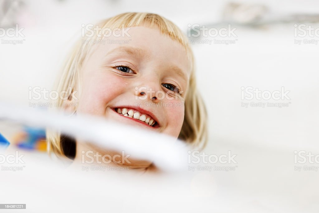 Cute 4 year old girl peeps over bath edge laughing stock photo