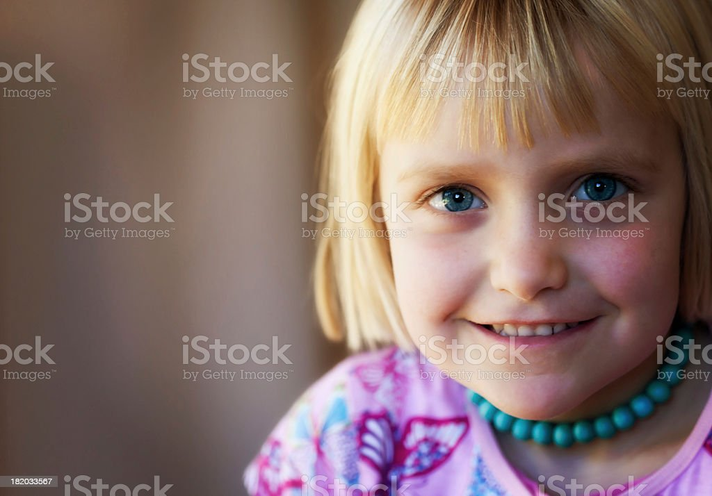 Cute 5 year old blonde girl smiles shyly stock photo