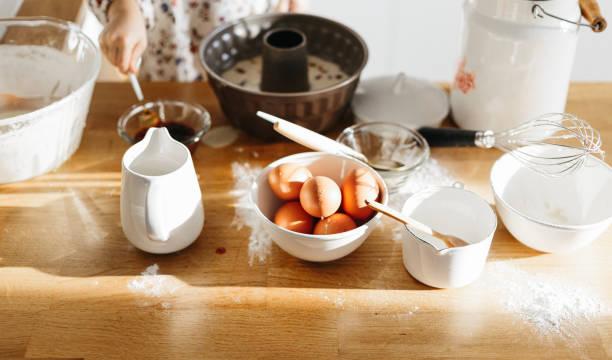 Süße 5 Jahre Mädchen tragen Kleid Vorbereitung Kuchen in der weißen modernen Küche. – Foto
