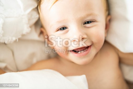 1084486306 istock photo Cute 8 months baby girl on bed on the morning 1074943056