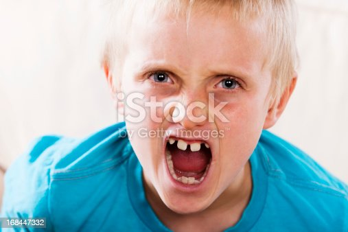 istock Cute 8 year old blond boy making a ferocious face 168447332
