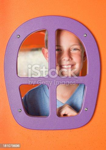A cute 9 year old boy peeking though a playhouse window.