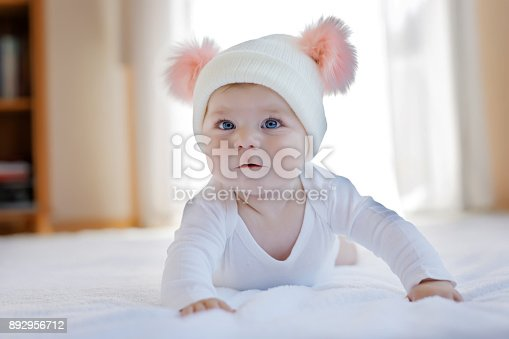 istock Cute adorable baby child with warm white and pink hat with cute bobbles 892956712