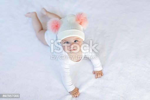 istock Cute adorable baby child with warm white and pink hat with cute bobbles 892957000