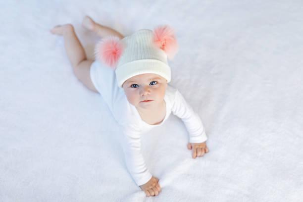 cute adorable baby kind mit weißen und rosa mütze mit süßen bommeln - festliche babymode junge stock-fotos und bilder