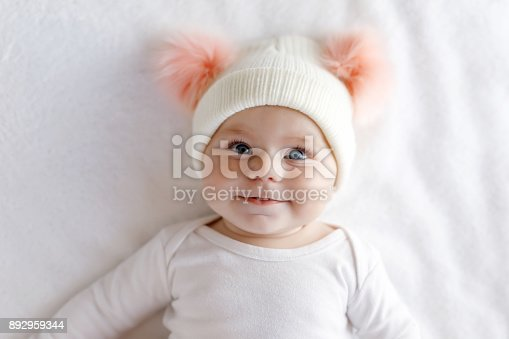 istock Cute adorable baby child with warm white and pink hat with cute bobbles 892959344