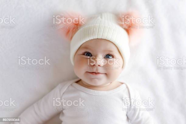 Cute adorable baby child with warm white and pink hat with cute bobbles. Happy baby girl on white background and looking at the camera. Close-up for xmas holiday and family concept.