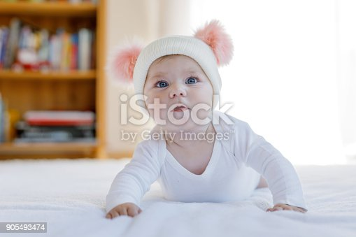istock Cute adorable baby child with warm white and pink hat with cute bobbles 905493474