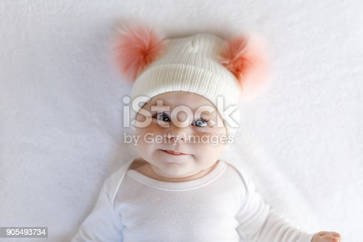istock Cute adorable baby child with warm white and pink hat with cute bobbles 905493734