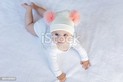 istock Cute adorable baby child with warm white and pink hat with cute bobbles 905493902