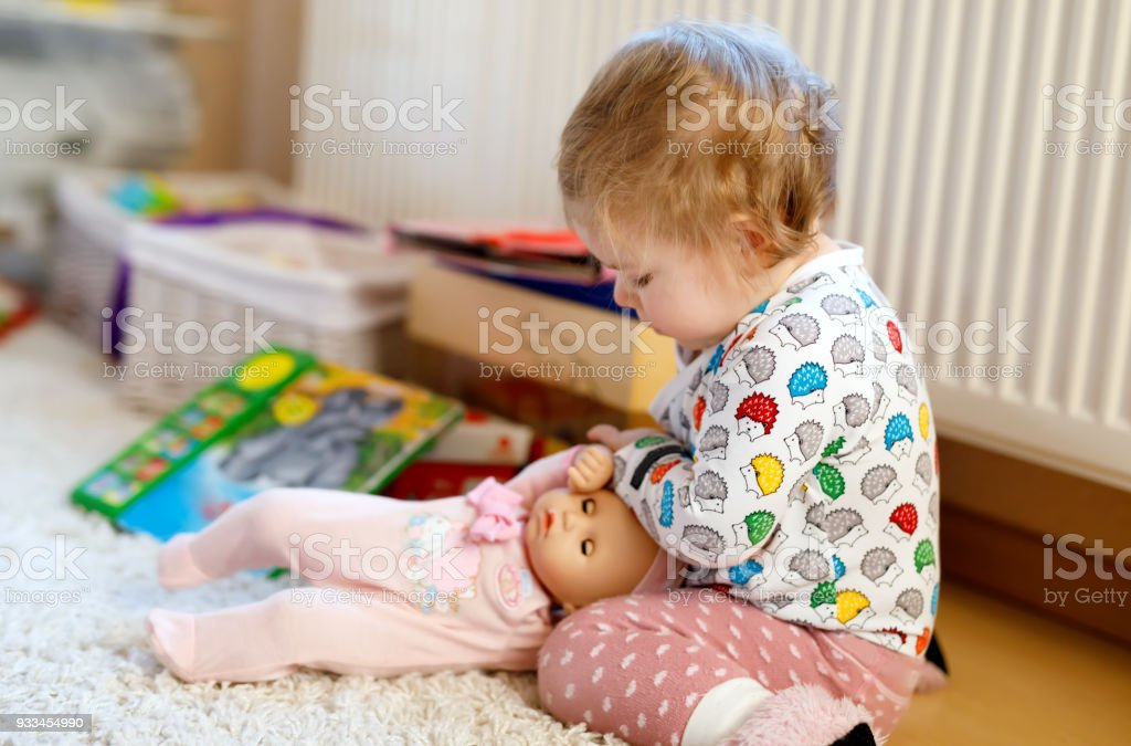 Cute adorable baby girl playing with first doll. Beautiful toddler child at home. stock photo