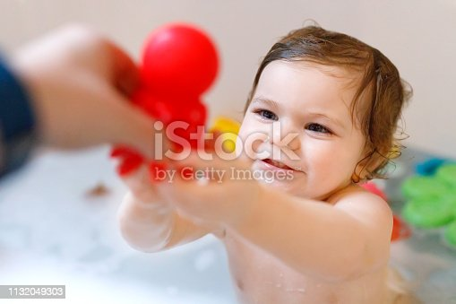 1134841078 istock photo Cute adorable baby girl taking foamy bath in bathtub. Toddler playing with bath rubber toys. Beautiful child having fun with colorful gum toys and foam bubbles 1132049303